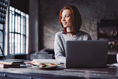 woman on laptop smiling towards window
